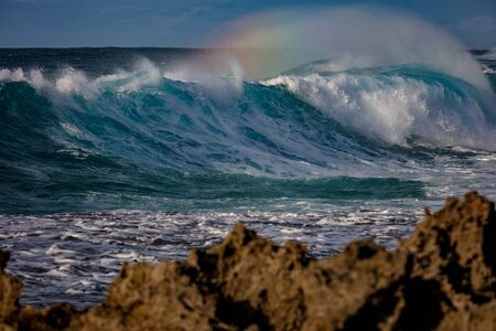 Rough Ocean Shorebreak Wave with rainbow on water dust