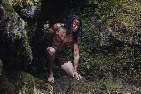 獲物を待っているナイフで野生の男先住民の野蛮な狩り