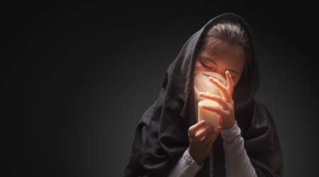 Mourning woman wearing black cloth holding candle with fire, the expression of deep sorrow for someone who has died during pandemic