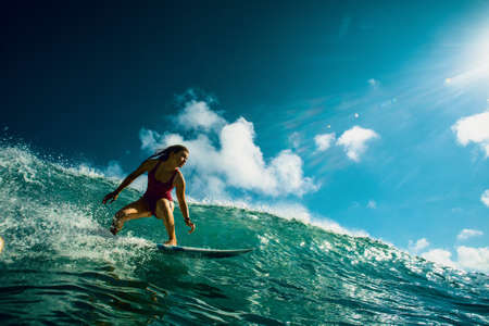 Professional Surfer Girl riding wave on surfing board under bright sun on background