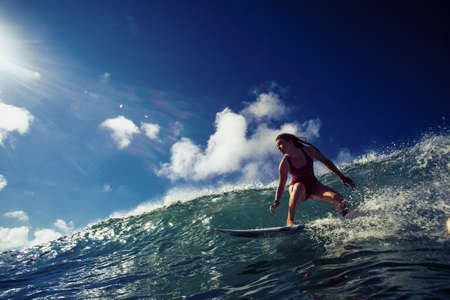 Professional Surfer Girl riding wave on surfing board under bright sun on background Archivio Fotografico - 151833693