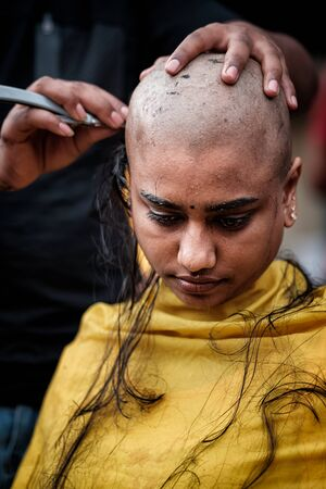 Close-up of young lady devotee getting tonsured or head shaving ritual in Thaipusam Festival.