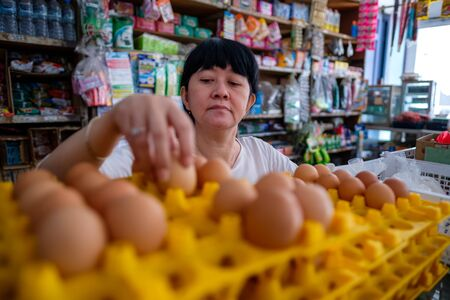 Asian Indonesian women arranging eggs inside small local family-owned business store, or locally called warung. Location is in Tasikmalaya, Indonesia. Selective Focus.
