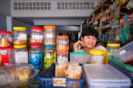 Asiatische indonesische Frauen vor einem kleinen lokalen Familienunternehmen, das vor Ort Warung genannt wird. Standort ist in Tasikmalaya, Indonesien. Selektiver Fokus.