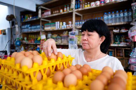 Femmes indonésiennes asiatiques organisant des œufs à l'intérieur d'un petit magasin familial local, ou appelé localement warung. L'emplacement est à Tasikmalaya, en Indonésie. Mise au point sélective.