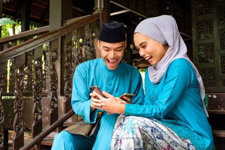 Young couple of malay muslim in traditional costume watching online content in a smart phone with happy expression during Eid al-Fitr celebration at wooden stair. Raya and Muslim fashion concept.