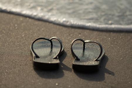 sandalias: sandalias negras cerca del mar