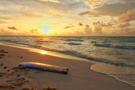 Surfboard on the beach at sunrise