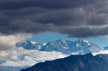 snowy andes mountain range among clouds
