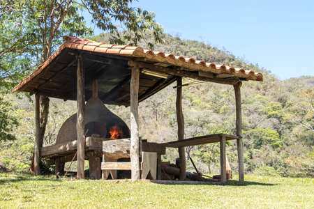 clay oven with burning fire under shelter