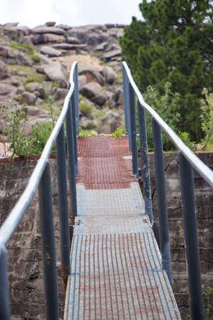 old gray iron footbridge with handrail