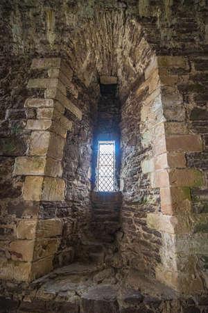little window between rocky walls in an old castle Standard-Bild