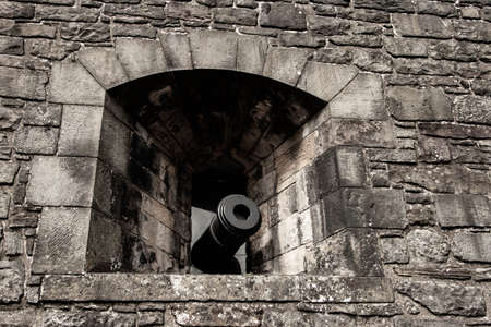 cannon in a castle pointing from a peephole