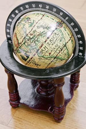 photography of antique globe on wood floor photo
