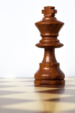 closeup of chess king piece over chessboard photo