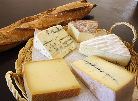 gruyere: Five different french and swiss cheese platter on a black table with a baton bread.