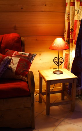 Romantic warm interior of a wooden chalet by night Stock Photo - 4220062