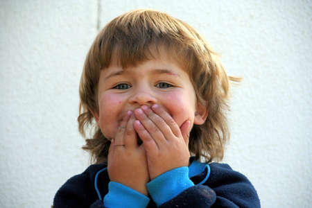 Boy laughing behind his hands Stock Photo