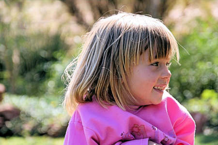 Portrait of a young girl playing outside in the garden, wearing a pink sweater