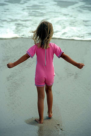 Young girl walking towards the sea, holding out her hands to show she is brave enough to walk alone