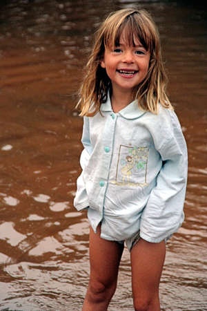 Portrait of a young girl standing with her clothes in a the rain water, holding up her trousers not to get wet.  Joy and exitement about the rain on her face.