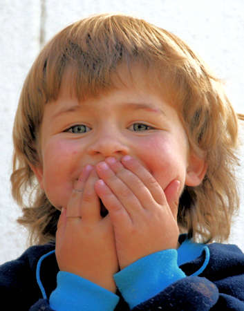 Portrait of a little boy playing outdoors, laughing and holding his hands accross his mouth, to hide his smile.
