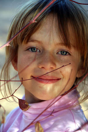 Portrait of a young girl playing in the trees in the garden Stock Photo