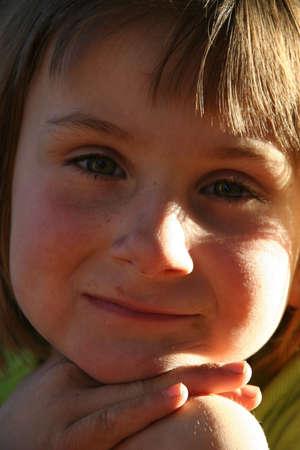 Little girl sitting in the sunlight, lighting her face