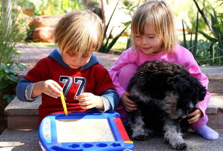 Portrait of a boy and girl, drawing and playing with their dog