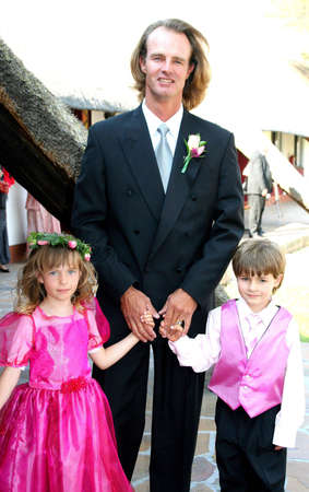 Portrait of a man holding the hands of his children at wedding reception Stock Photo