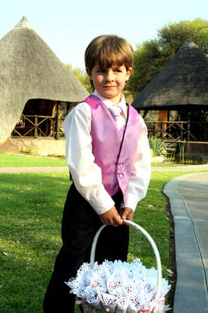 Portrait of a page boy at a wedding wearing pink waistcoat