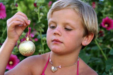 Portrait of a girl holding a golden christmas ball