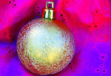 Golden Christmas ball agains pink dress fabric