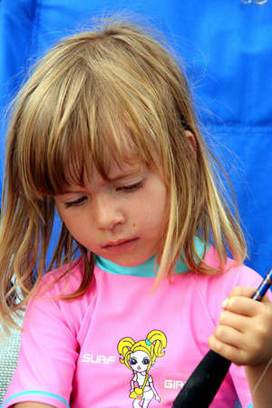 Portrait of a girl sitting in a blue chair, holding a fishing rod