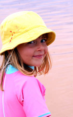 Portrait with a girl wearing pink hat and swimsuit at the beach