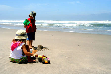 Portrait of two children playing with toys on the beach Stock Photo