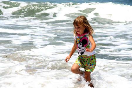 portrait of a little girl running in the waves at the beach Stock Photo