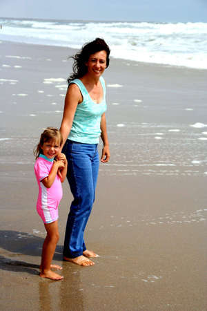 Portrait of a mother and daughter walking on the beach