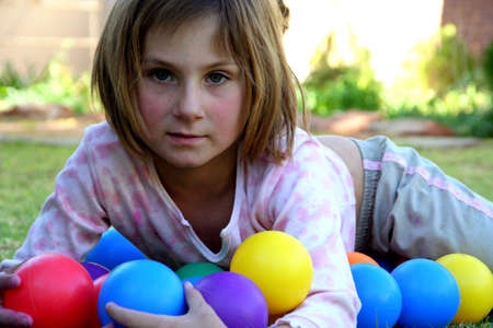 portrait of a young girl lying on the grass, holding coloured balls