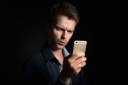 Man checking out his mobile phone in the dark Stock Photo
