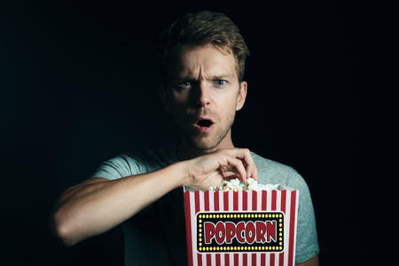 Man watching television with popcorn Stock Photo - 81358511