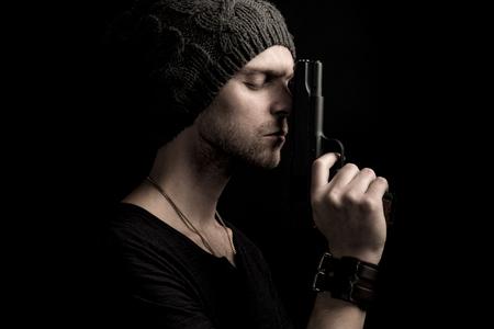 Man with hat holding a handgun in the dark Imagens