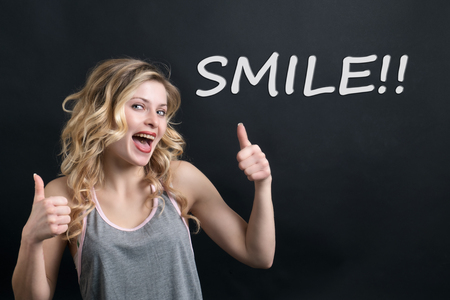 Young woman smiling with thumbs up