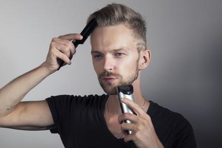 Handsome man shaving beard and combing hair Reklamní fotografie