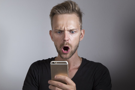Shocked man looking at his mobile phone