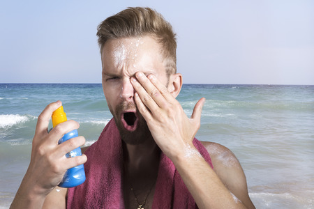 Man spraying sun lotion in his eyes on the beach Reklamní fotografie