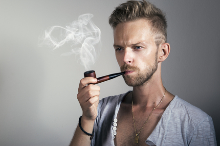 Handsome man smoking a pipe