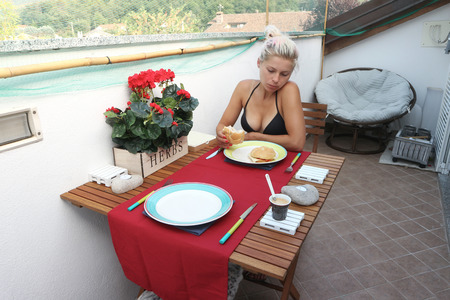 Young woman having breakfast on the balcony
