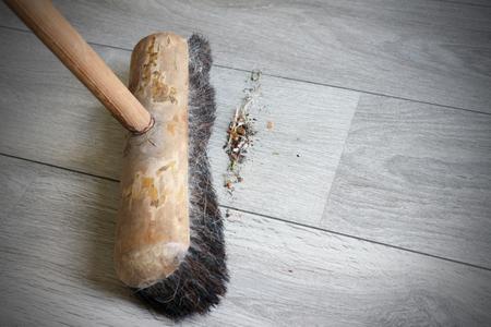 Wooden groom sweeping dirt on the floor