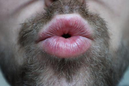 Man with facial hair giving kiss Foto de archivo